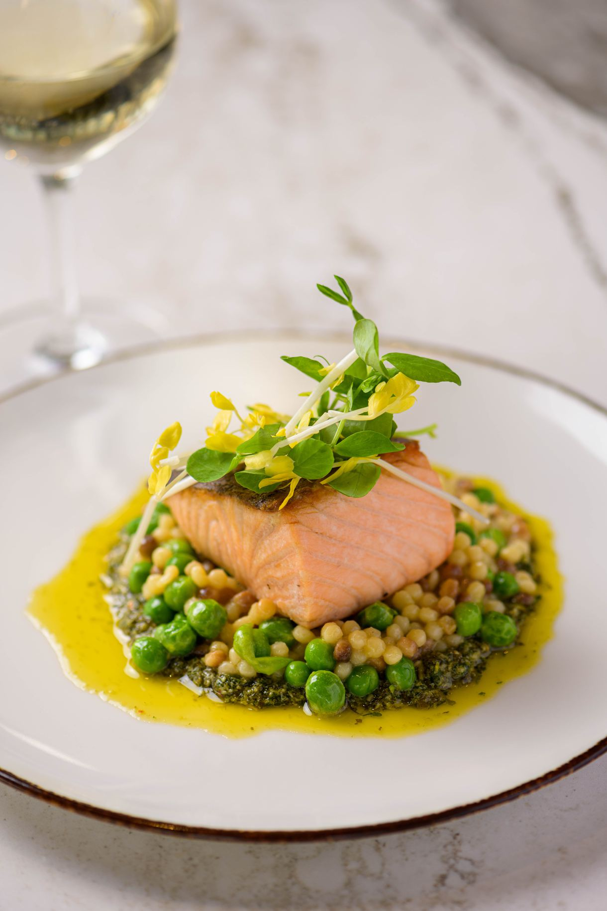 Fresh salmon crowns a bed of Sardinian pasta, peas, and basil pesto. Photo by Chris Schmauch.