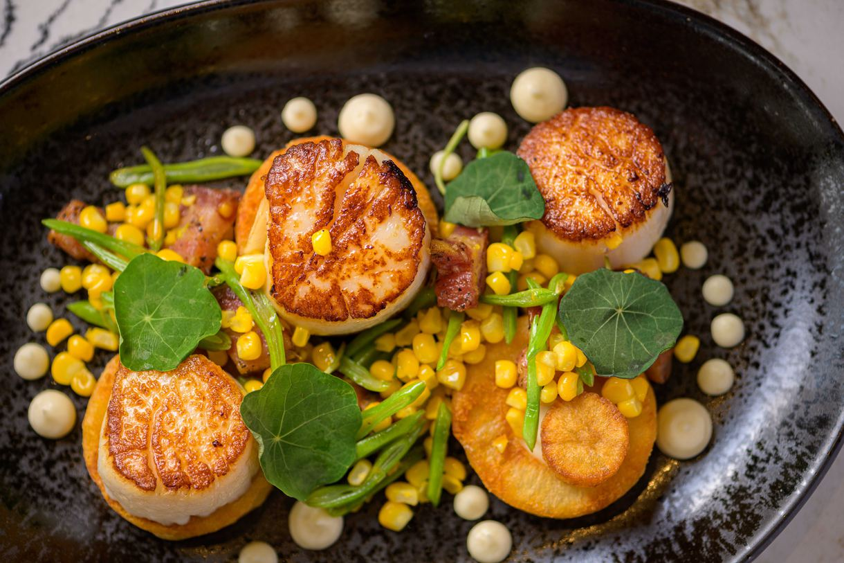 Perfectly seared sea scallops are enhanced only by sweet corn kernels and crispy pancetta. Photo by Chris Schmauch.