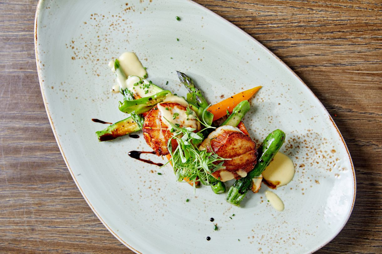 Seared diver scallops are intermingled with seasonal vegetables and miso and lima bean puree.