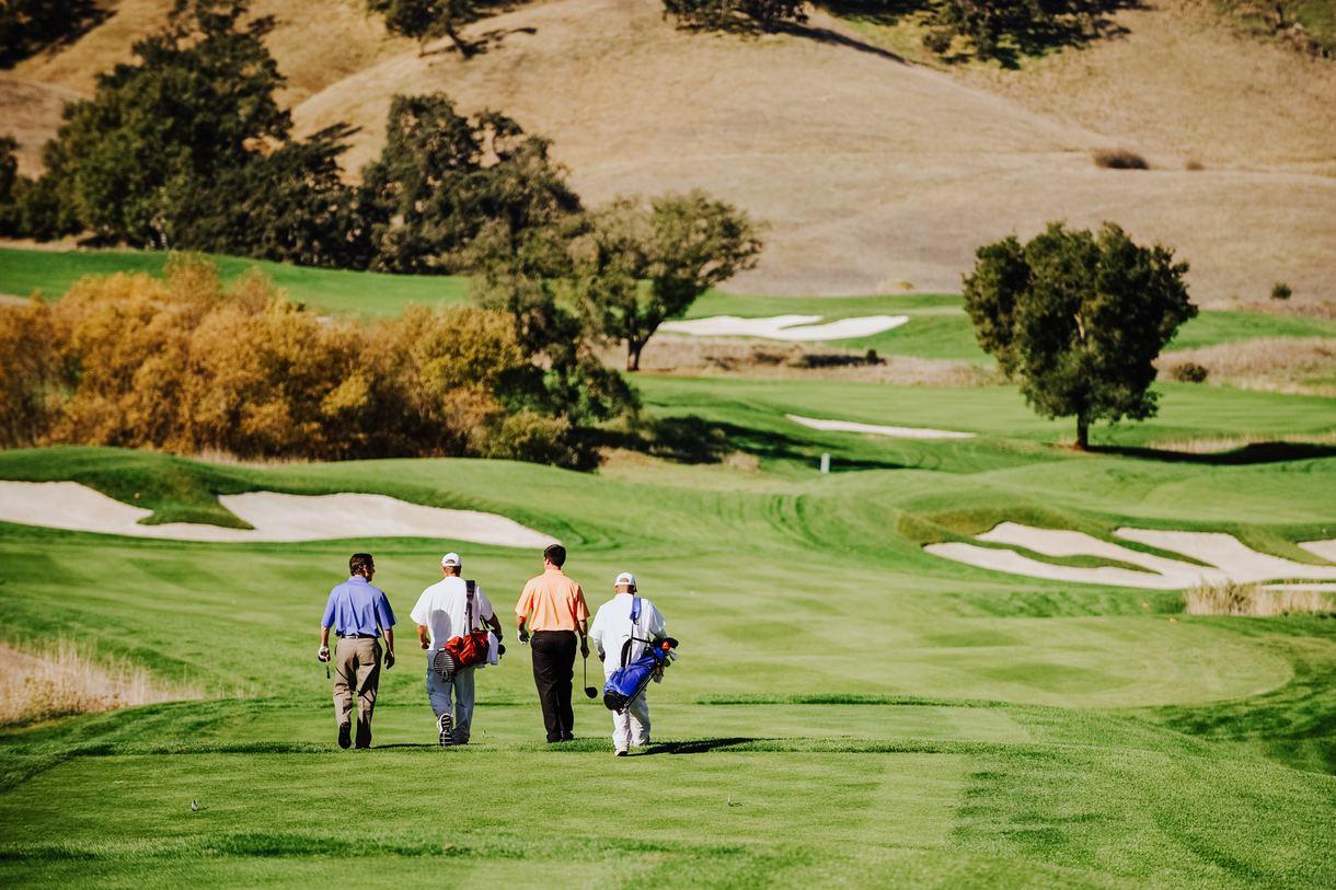 Golfers walk the fairway